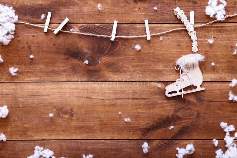 Jeździć na łyżwach na zimy pojęciu, biały lodowej łyżwy obwieszenie na drewnianym brown tle z płatkami śniegu, odgórny widok z ko zdjęcia stock