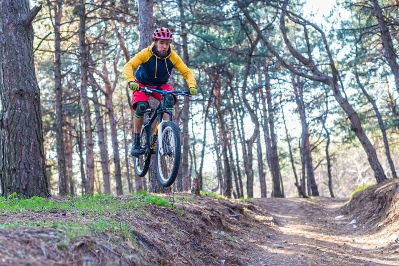 Jeździć na rowerze na krawędzi skłonu, cyklista w jaskrawej odzieżowej jazdie rower górski aktywny tryb życia fotografia stock