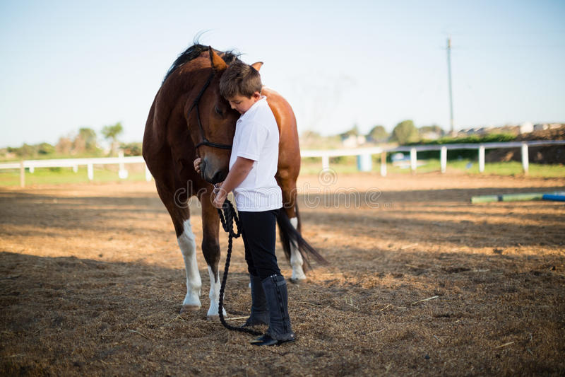 Jeździec chłopiec pieści konia w rancho obrazy royalty free