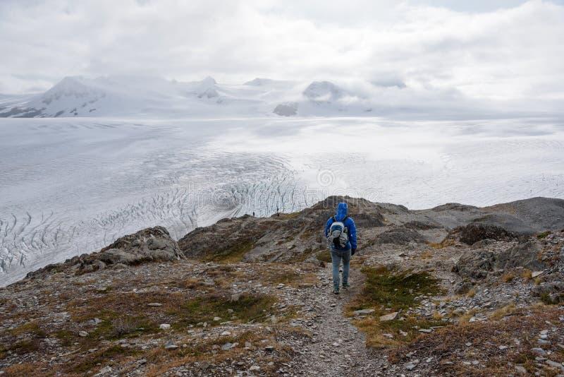Jeździec z niebieską kurtką na Harding Glacier Trail, Exit Glacier, Park Narodowy Kenai Fjords, Seward, Alaska, Stany Zjednoczone zdjęcia stock