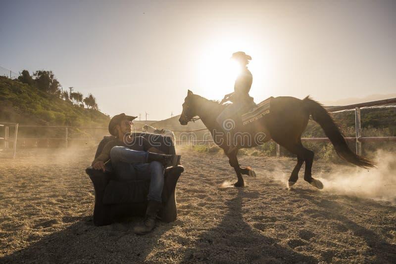 Jeźdzowie z koniami w złotym zmierzchu zaświecają mężczyzny obsiadanie na starym siedzeniu i kobiety przejażdżka wokoło on robi p obraz stock