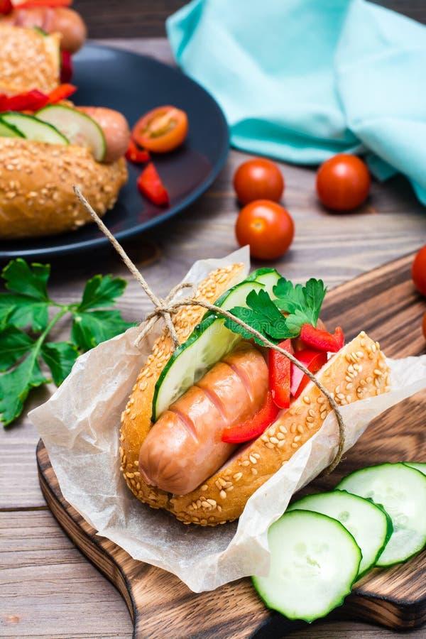 Je apetycznego hot dog robi? od sma??cej kie?basy, rolek i ?wie?ych warzyw zawijaj?cych w pergaminowym papierze, na tn?cej desce fotografia stock
