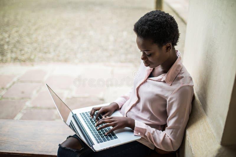 Je dois vérifier de l'information Jolie fille d'étudiant à l'aide de l'ordinateur portable pour le travail au campus images libres de droits