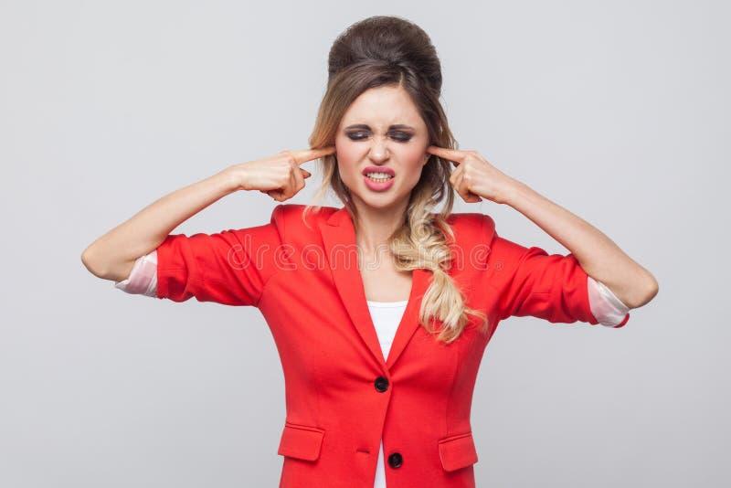 Je mets le ` t veux entendre Dame nerveuse d'affaires avec la coiffure et le maquillage dans le blazer de fantaisie rouge, se ten images libres de droits