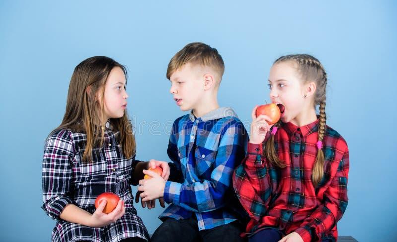 Je owoc i jest zdrowy Promować zdrowego odżywianie Chłopiec i dziewczyna przyjaciele jemy jabłka   grupa zdjęcia royalty free