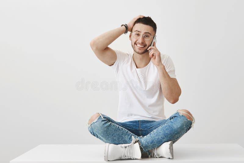 Je suis si heureux vous ai appelé Portrait de studio d'homme bel ordinaire avec la barbe en verres, se reposant sur le plancher a images stock