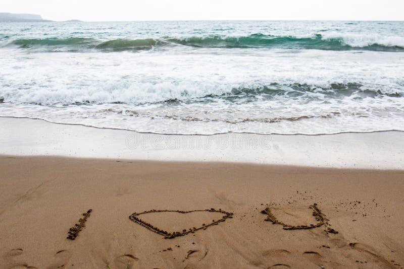 Je t'aime dessiné dans le sable d'une plage grecque avec de l'eau turquoise images libres de droits