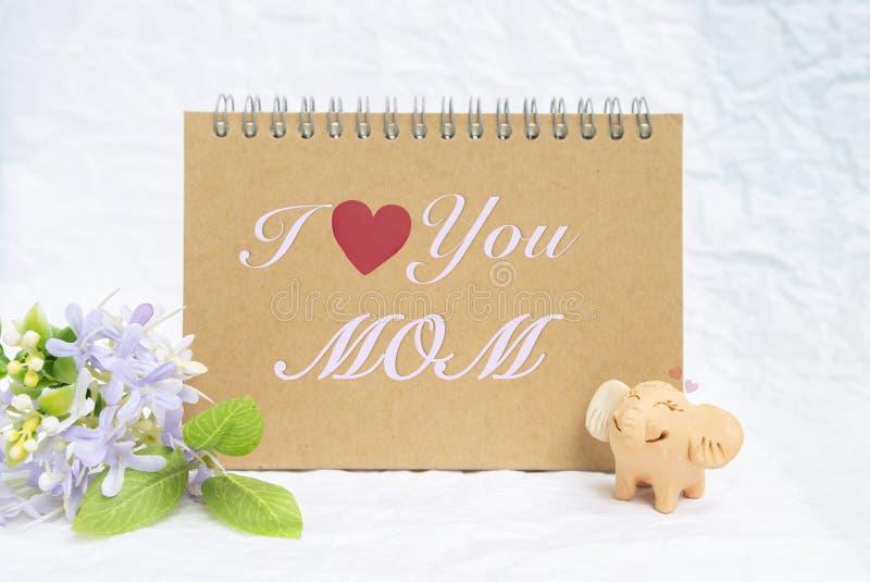 Je t'aime maman sur le carnet brun vide avec l'éléphant et la fleur de sourire image libre de droits