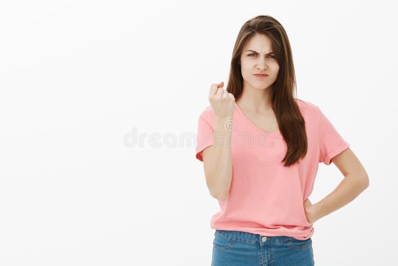 Je te montrerai comment désobéissez Portrait de femelle mignonne déçue dans l'équipement occasionnel, tenant la main sur la hanch photos libres de droits
