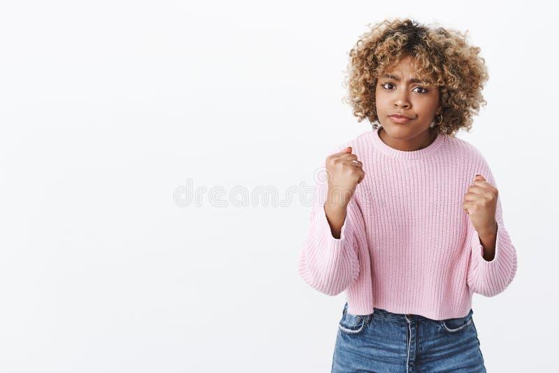 Je vous montrerai, viens plus ?troitement Portrait de blonde f?ch?e et mignonne d'afro-am?ricain dans le froncement de sourcils d photo libre de droits