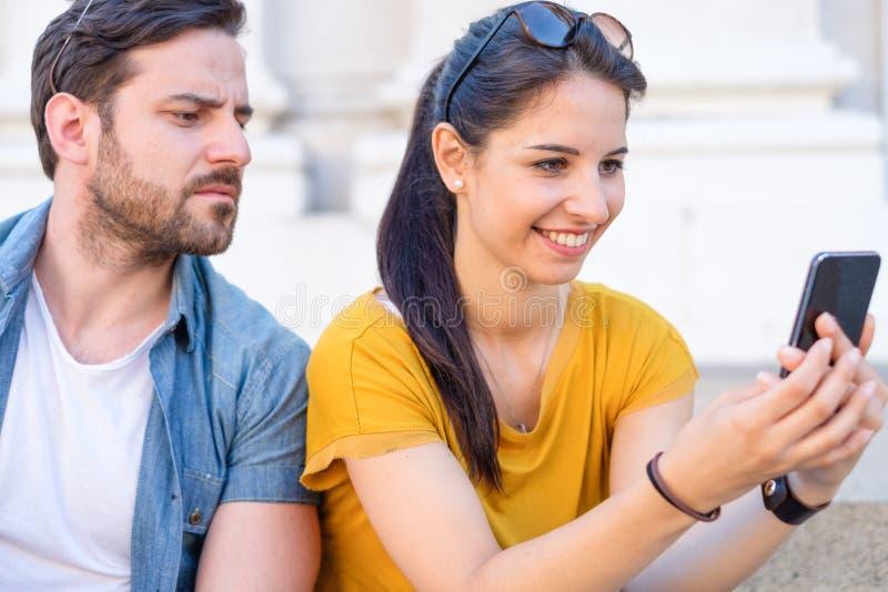 Jealous boyfriend looking her girlfriend chatting royalty free stock photography