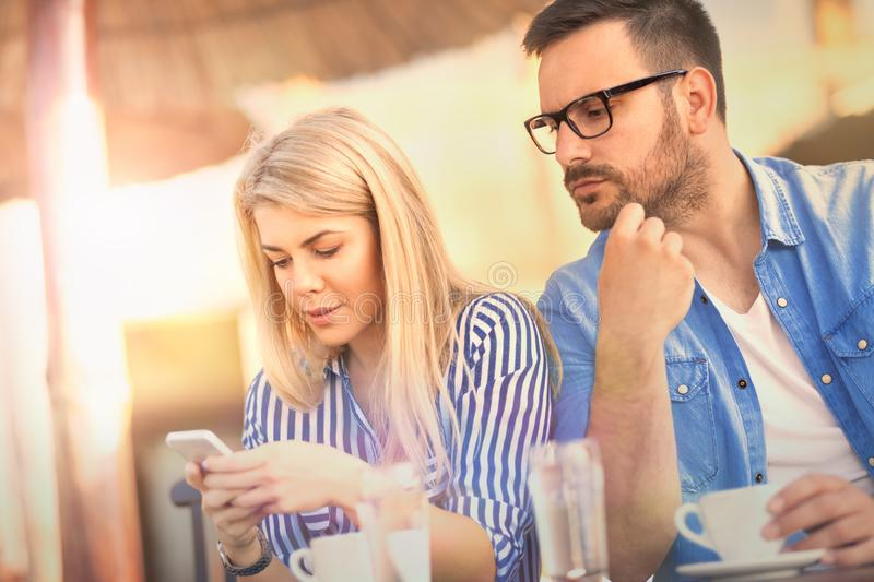 Jealous girl spying her boyfriend`s mobile phone while he typing stock photos