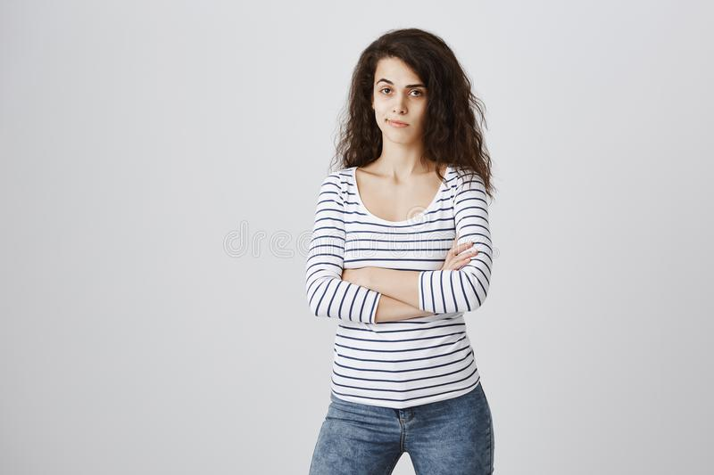 Jealous girlfriend being suspicious. Indoor shot of beautiful curly-haired caucasian girl standing with crossed hands royalty free stock photo
