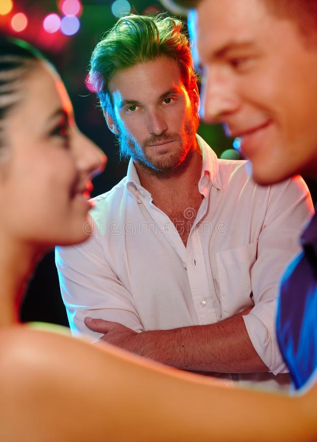 Jealous man looking at dancing couple royalty free stock photography