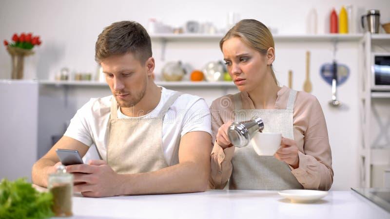 Jealous woman peeping in husbands smartphone, relationship crisis, distrust stock photo