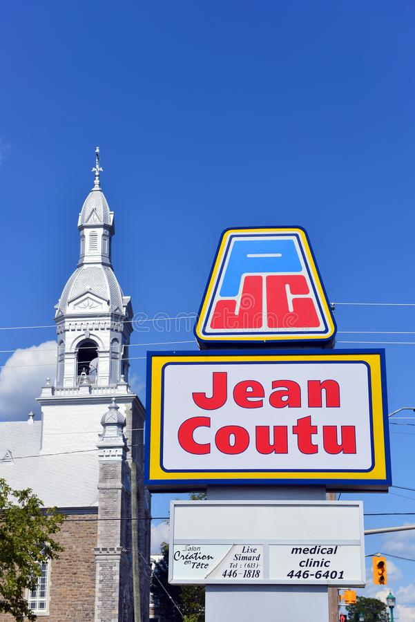 Jean Coutu sign and Catholic Church. Rockland, Canada - August 13, 2017: Sign for Jean Coutu on Laurier St. The drug store chain with 400 over stores in Quebec royalty free stock photography