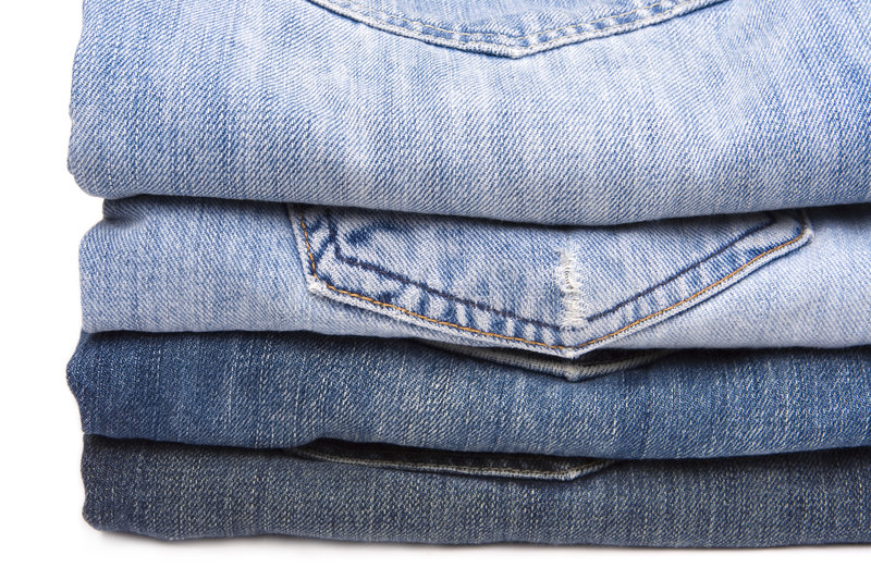 Jeans. Close up of jeans stocked one on top of another isolated on a white background royalty free stock image