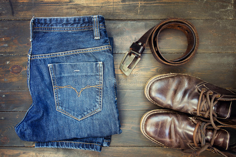 Jeans belt and shoes set on wood. En board royalty free stock photography