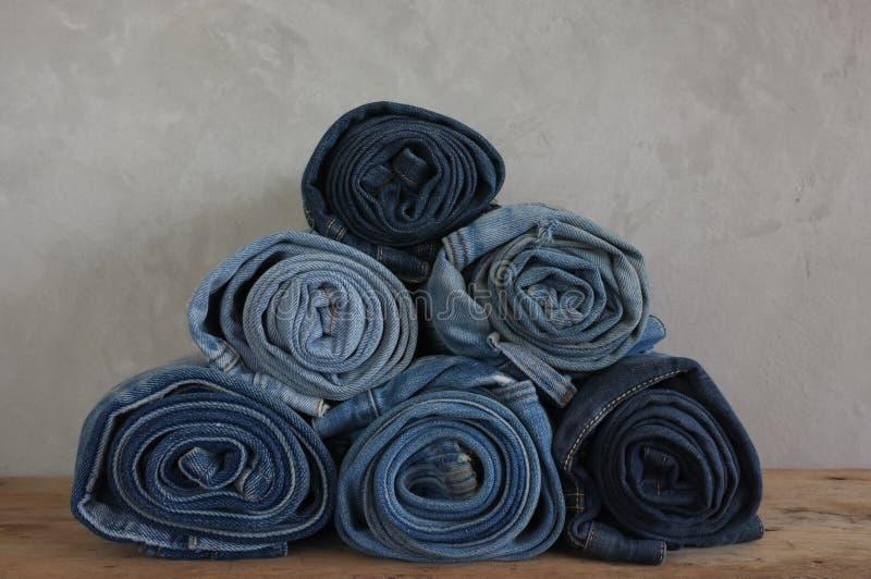 Jeans bleus de denim de petit pain de pile sur le bois photographie stock