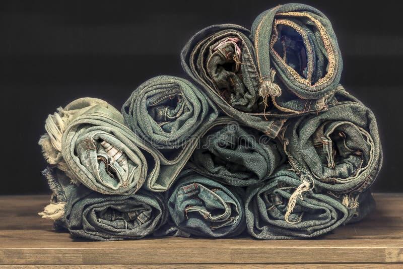 Jeans blu del denim del rotolo sistemati in pila Sul fondo di struttura di legno di quercia, Jeans strappati di uno spazio della  fotografia stock libera da diritti