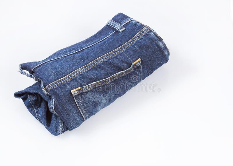 Jeans in broodje worden op witte achtergrond wordt geïsoleerd verdraaid die stock afbeeldingen