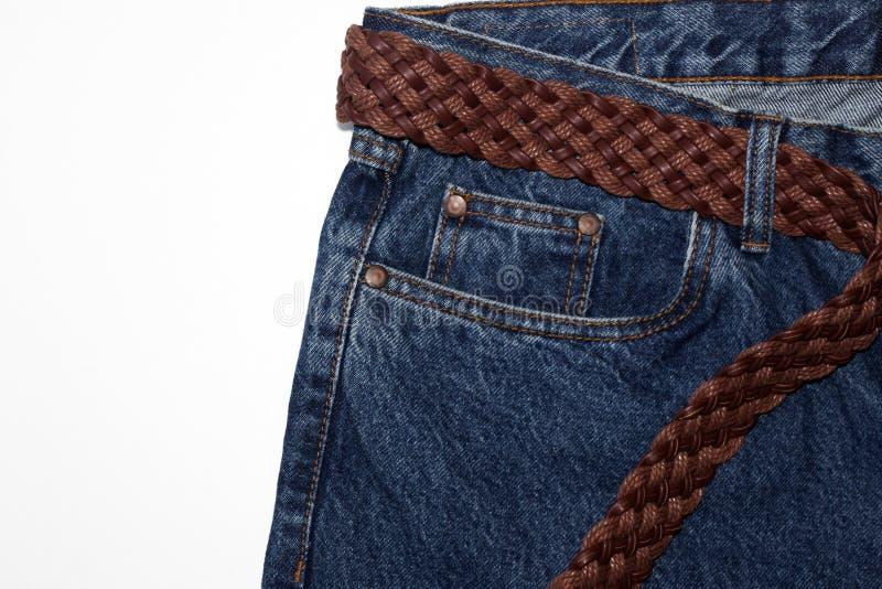 Jeans classiques avec cinq poches en gros plan jeans avec une ceinture tissée de cuir brun et de fils épais bruts bleu de cru tex image stock