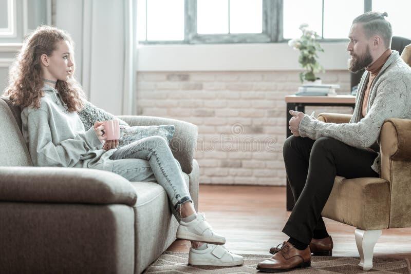 Jeans d'uso della bella ragazza che parlano con suo consulente privato fotografia stock libera da diritti