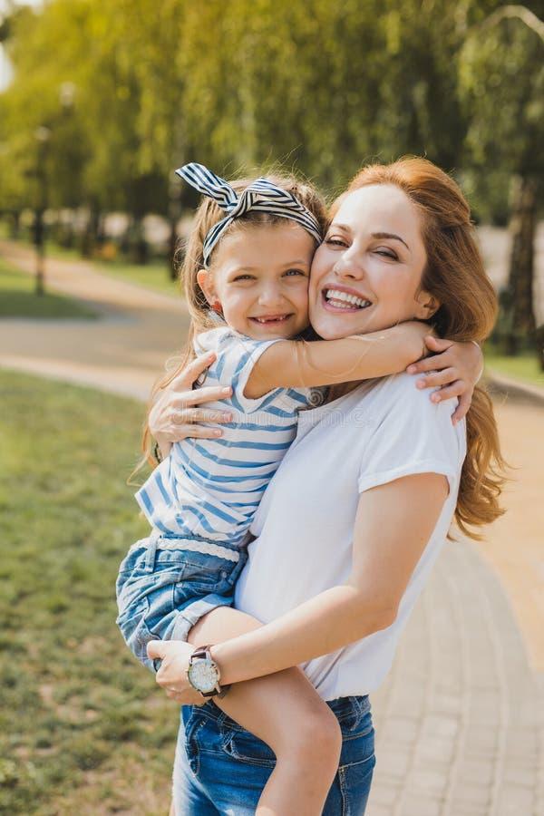 Jeans d'uso della madre alla moda e camicia bianca che tengono la sua bambina fotografie stock libere da diritti