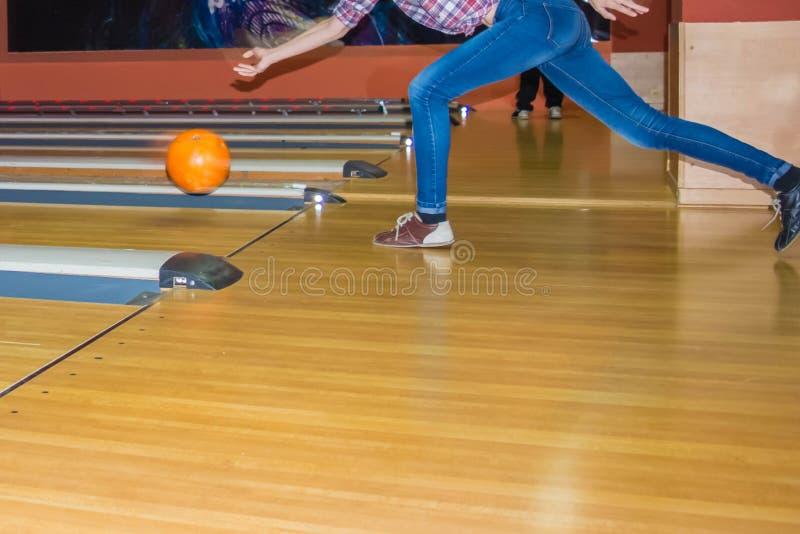 Jeans d'uso della ragazza che giocano bowling fotografia stock
