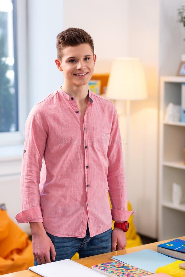 Jeans de port d'adolescent et position rose de chemise près de la table images stock
