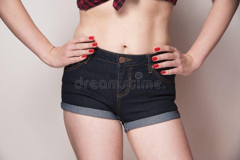 Jeans de port de femme avec ses mains sur des hanches photos stock