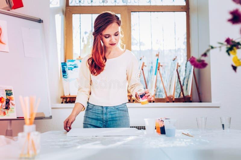 Jeans de port de professeur d'art et position beige de chemise dans le studio de peinture image libre de droits