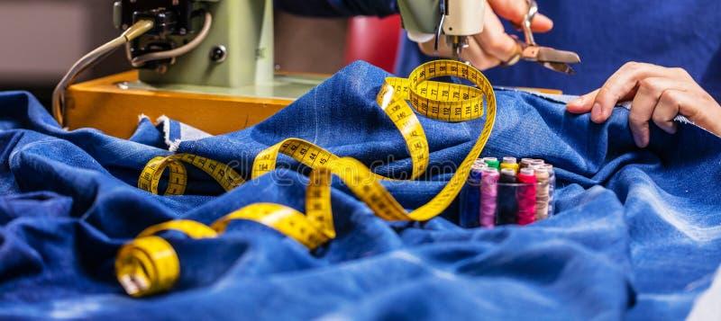 Jeans di cucito del denim con la macchina per cucire Jeans di riparazione tramite la macchina per cucire Jeans di alterazione, or immagini stock libere da diritti