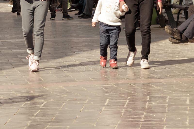 Jeans di due persone e ragazza d'uso del bambino che indossa abbigliamento di lana che cammina tramite il viale pedonale nelle va immagine stock libera da diritti