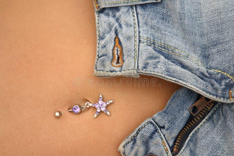 Jeans e piercing del bellybutton fotografia stock