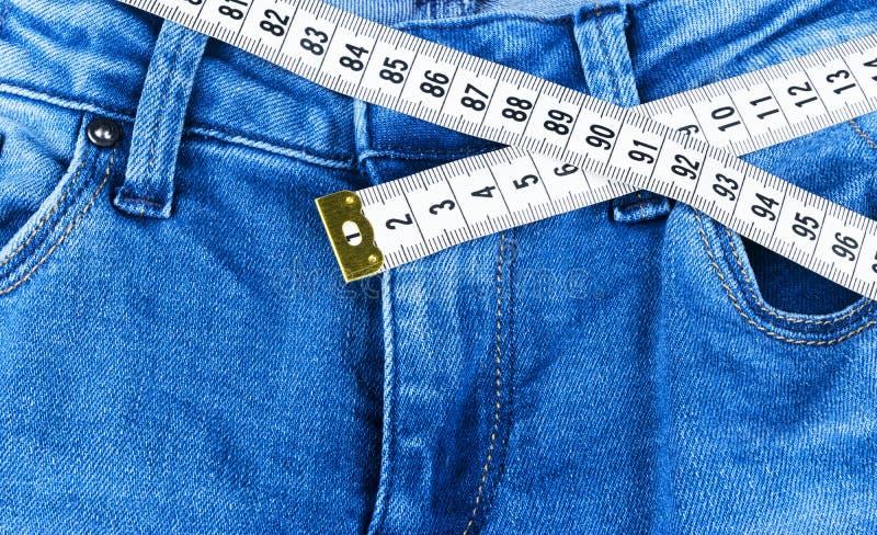 Jeans et règle d'une femme de bleu, concept de régime et perte de poids Jeans avec la bande de mesure Mode de vie sain, suivant u images libres de droits