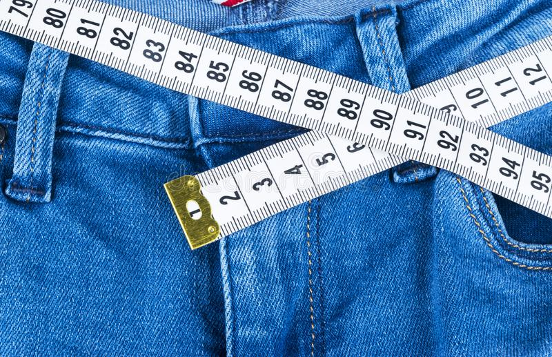 Jeans et règle d'une femme de bleu, concept de régime et perte de poids Jeans avec la bande de mesure Mode de vie sain, suivant u photo libre de droits
