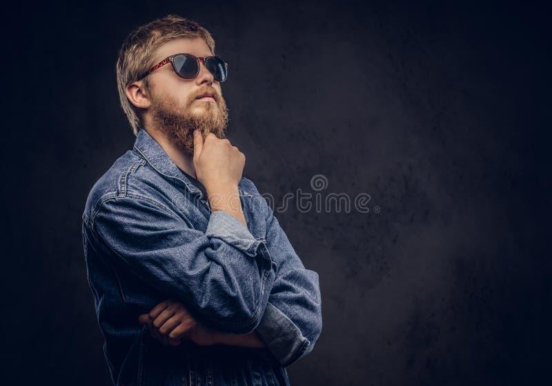 Jeans för solglasögon för eftertänksam hipstergrabb klår upp bärande iklädd att posera med handen på hakan på en mörk bakgrund royaltyfria foton