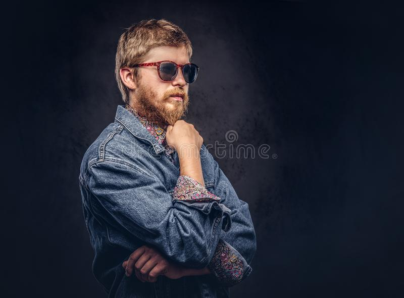 Jeans för solglasögon för eftertänksam hipstergrabb klår upp bärande iklädd att posera med handen på hakan på en mörk bakgrund royaltyfria bilder