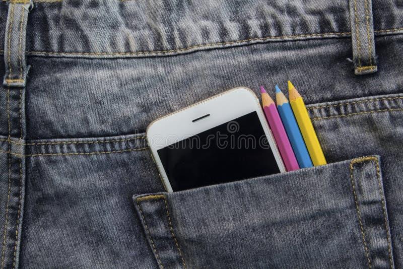 Jeans gris avec les crayons blancs de smartphone et de couleur dans la poche noire photos stock