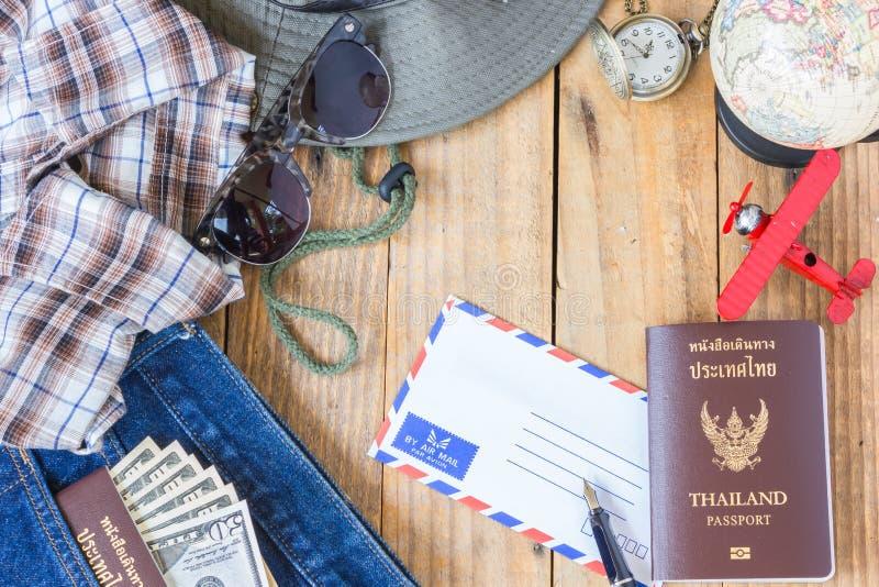 Jeans, Hemd, Pässe, Banknote, Sonnenbrille, Flugzeugmodell lizenzfreies stockfoto