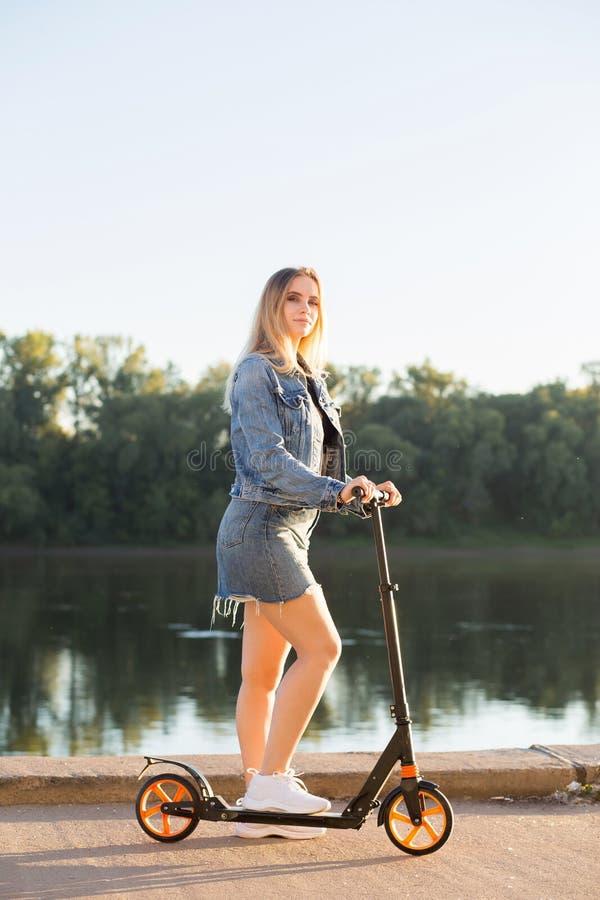 Jeans, kjol och rida för härlig kvinna bärande en sparkcykel arkivfoto