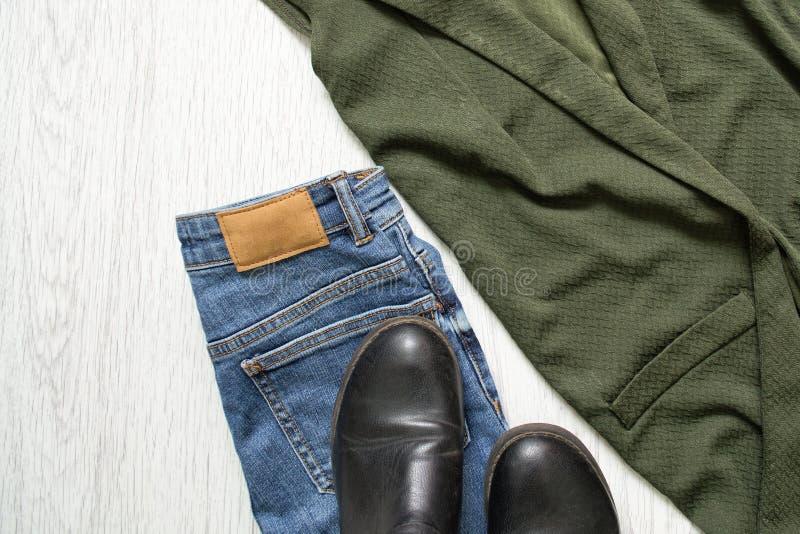 Jeans, laarzen en een groen jasje details Modieuze conce stock fotografie