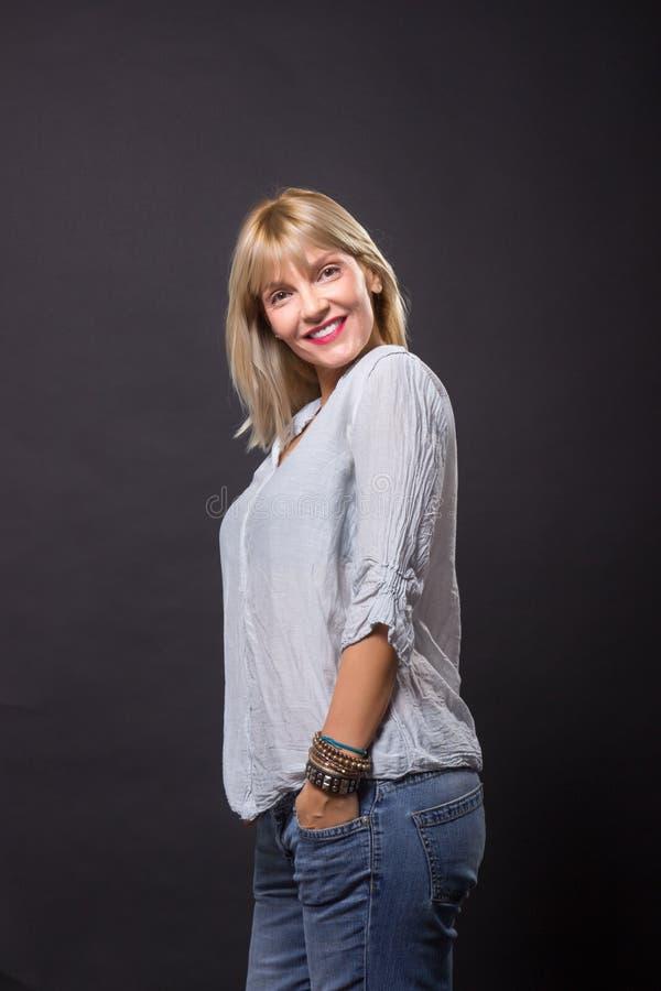Jeans mûrs gais de chemise de vêtements sport de la femme 40s image stock