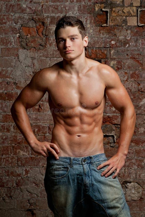 jeans man muskulöst naket posera sexigt barn arkivfoto