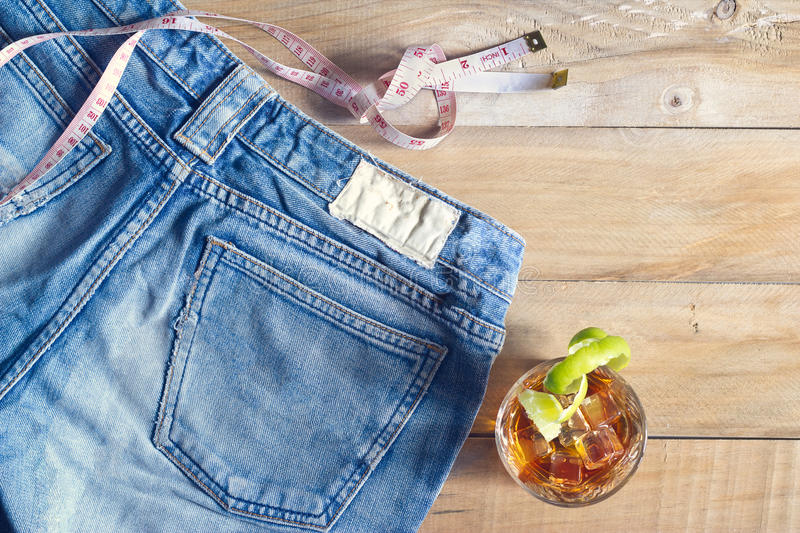 Jeans with measure and whiskey in glass on wooden royalty free stock photos
