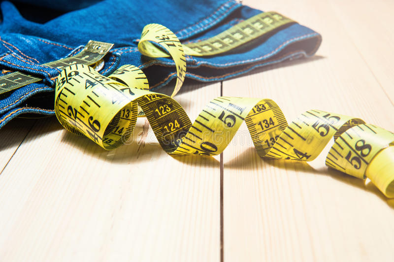 Jeans and a measuring tape.Concept of loosing weight.fruits for weight loss. Jeans and a measuring tape.Concept of loosing weight stock image