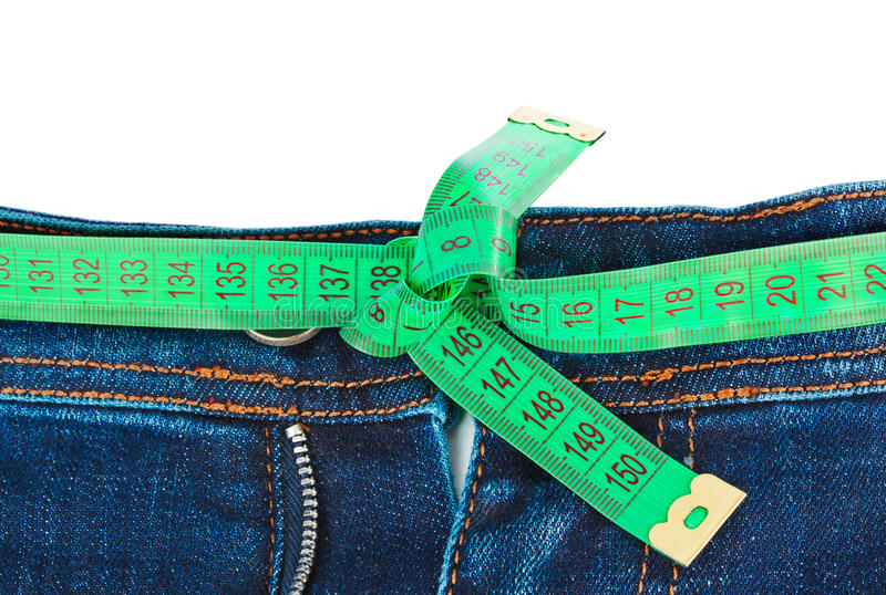 Jeans and measuring tape - slimming concept. Isolated on white background royalty free stock photos