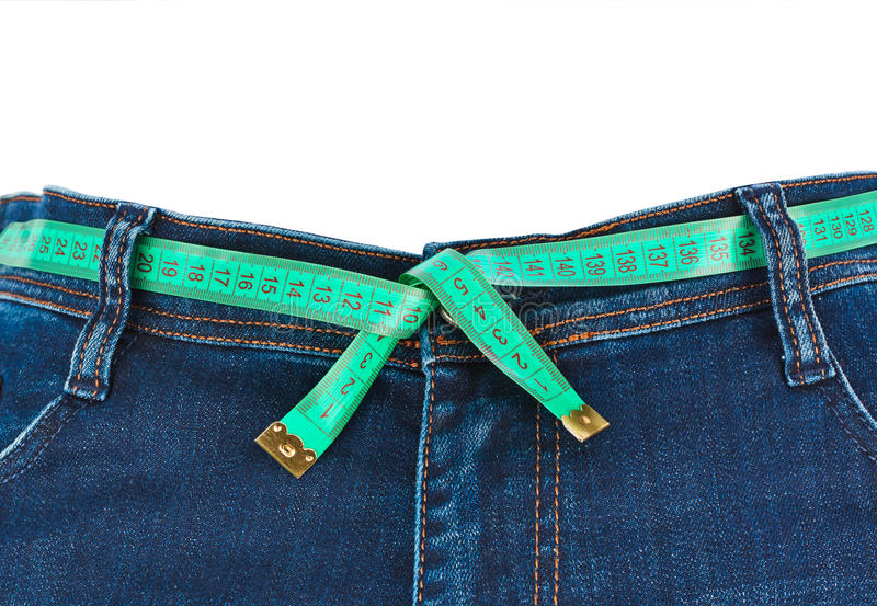 Jeans and measuring tape - slimming concept royalty free stock photography