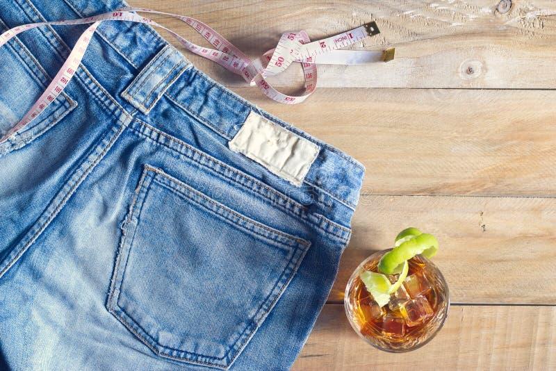 Jeans med mått och whisky i exponeringsglas på trä royaltyfria foton